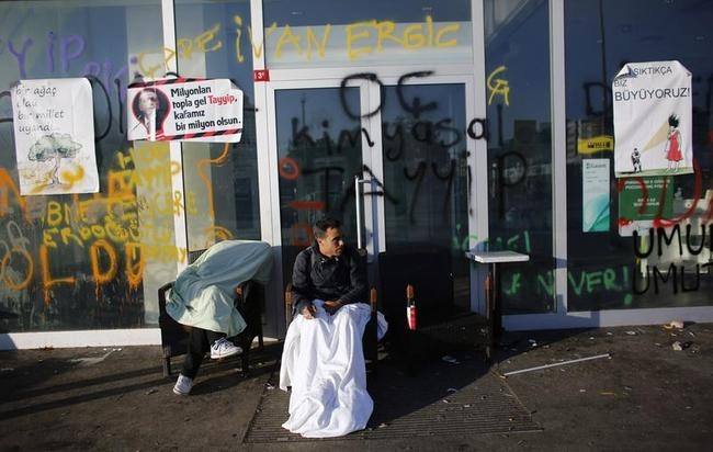 Protesters rest outside a bank at Taksim Square in central Istanbul