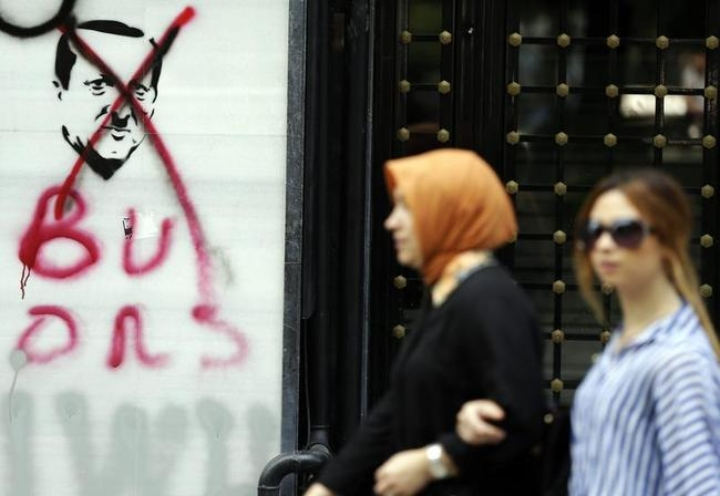 Women walk past graffiti depicting Turkish PM Erdogan in Istanbul
