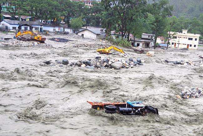 Vehicles are drifted away by the flood waters after cloud bursts and rains in Uttarkashi district