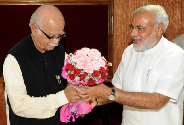 In this photograph taken on May 24, 2009, senior leader of India's opposition Bharatiya Janata Party (BJP) L.K. Advani (C) is given flowers by Chief Minister of the western state of Gujarat Narendra Modi (R) during a function at Circuit House in Ahmedabad.