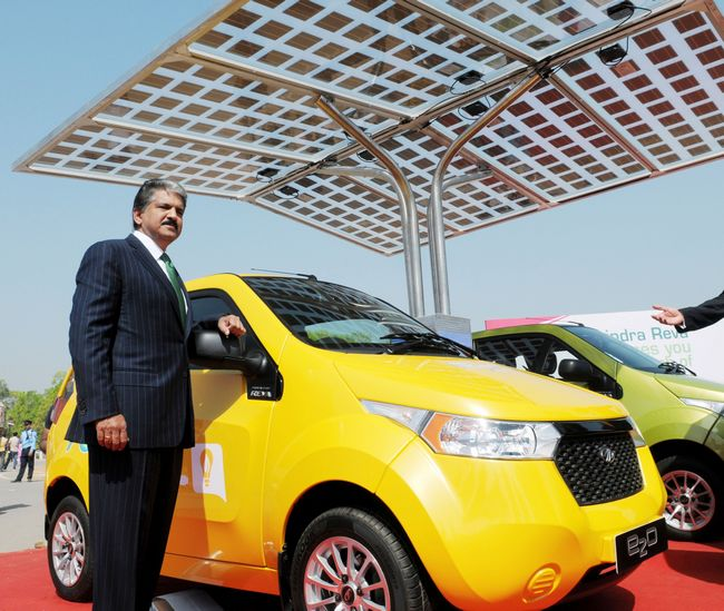 Mahindra & Mahindra launched the latest model of the electric car Reva, called Reva e2o (Ee-two-oh) for Rs 5.96 lakh yesterday. In the picture, Chairman and Managing Director of Mahindra and Mahindra, Anand G. Mahindra poses with newly launched Mahindra Reva 'e2o' car at India Gate in New Delhi.