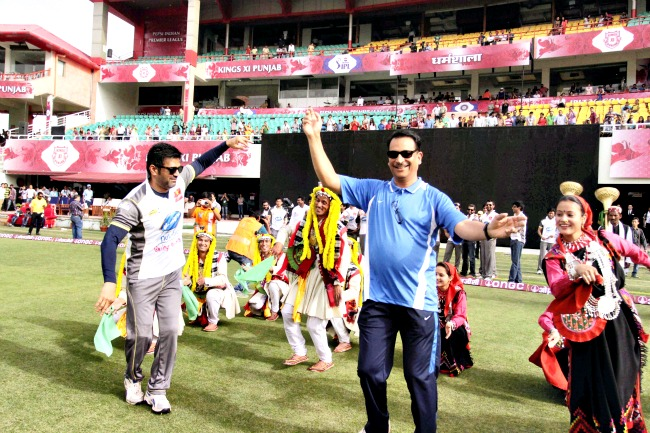 Actor Suniel Shetty and BJP leader Rajiv Partap Rudy dance with traditional Himachali artists before the start of a celebrity cricket match at the HPCA Stadium in Dharamshala on Monday. (Photo: PTI)