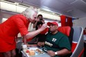 British entrepreneur Branson, who wears an AirAsia stewardess uniform, serves AirAsia's Chief Executive Fernandes during an AirAsia promotional event on a flight from Perth to Kuala Lumpur