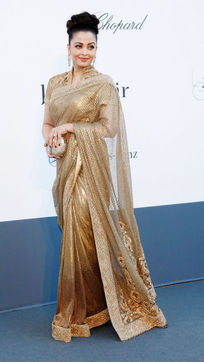 At the amFar gala, Ash appeared in a golden Tarun Tahiliani sari. The look was too blingy and she once again repeated her hair updo.