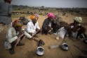 Camel traders wearing traditional headgear drink as they sit in a group at Pushkar Fair in the desert Indian state of Rajasthan