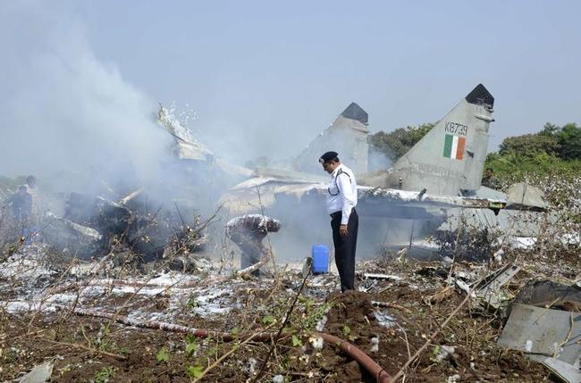 Firefighters douse a damaged MiG-29 aircraft of the Indian Air Force after a crash near Jamnagar