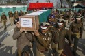 India's Central Reserve Police Force (CRPF) officers carry a coffin containing the body of a colleague during a wreath laying ceremony at a camp in Humhama