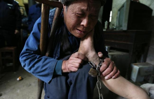 A boy's grandfather cries as he holds his foot, which is chained to a pillar, at their home in Zhejiang province
