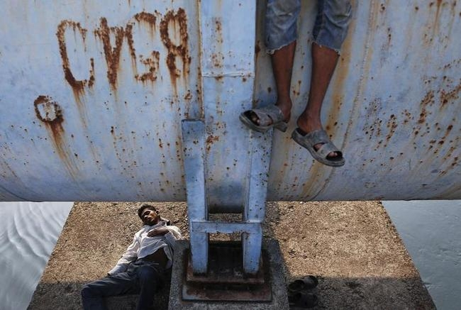 A man sleeps under a water pipeline as another stands on it in Mumbai