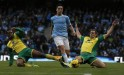 Manchester City's Nasri is challenged by Norwich City's Fer