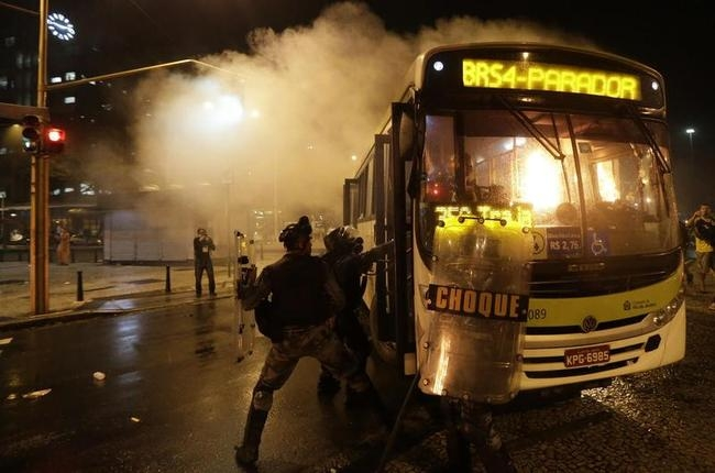 Riot policemen try to extinguish a fire in a bus after demonstrators from the group Black Bloc set fire to it during a protest in Rio de Janeiro