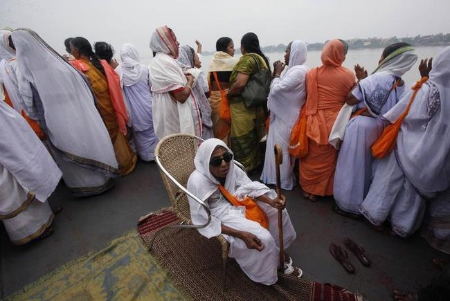 A widow sits on a chair as others chant hymns while travelling on a boat on their way to visit the Belur temple ahead of the Durga Puja festival on the outskirts of Kolkata