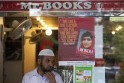 Man walks past a poster advertising Malala Yousufzai's book