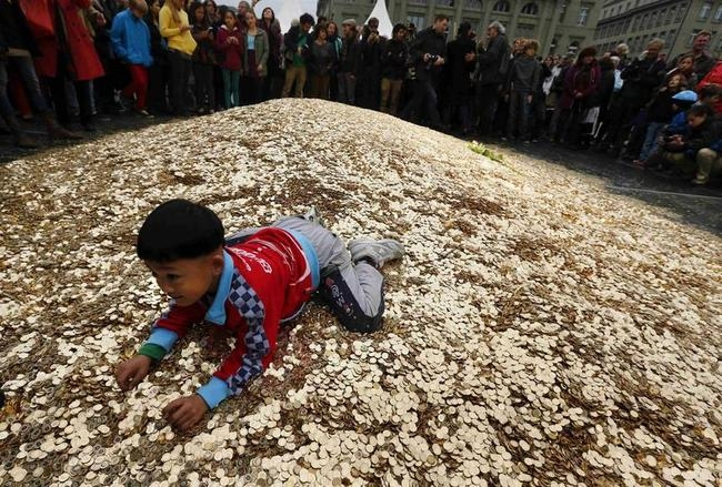 A child plays on a pile of 8,000,00 five cent coins in the centre of the Federal Square during an event organised by the Committee for the initiative Grundeinkommen in Bern