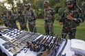 Indian army soldiers stand behind a display of seized arms and ammunition at a garrison in Srinagar