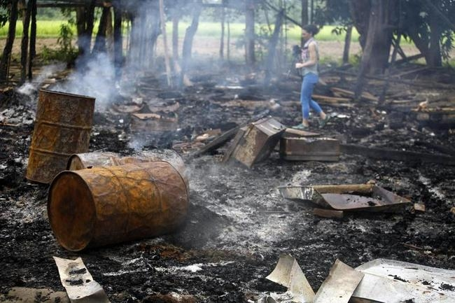 A journalist walks amongst the burnt-out remains of houses at Shwe Lay village
