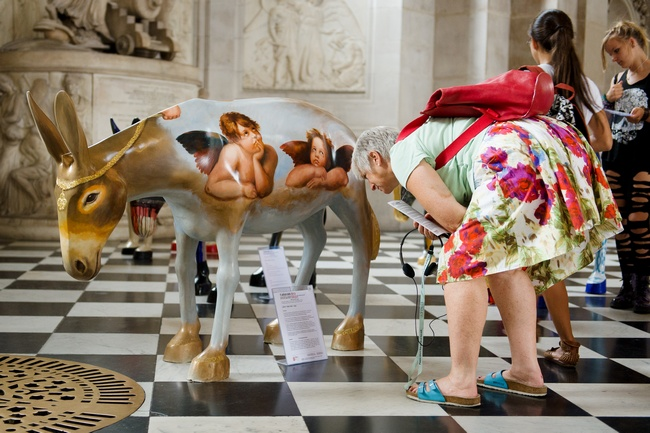 People explore some of the 25 life-size painted donkeys, created by Egyptian and Western artists, as they go on display in St Paul's Cathedral in London on August 30, 2013. An exhibition of 25 life-size painted donkeys entitled the