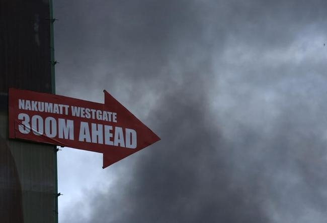 A sign pointing to the direction of Westgate shopping centre is pictured as smoke rises in the vicinity in Nairobi