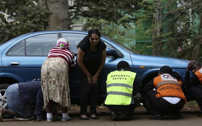 People take cover after hearing gun shots near the Westgate shopping centre in Nairobi