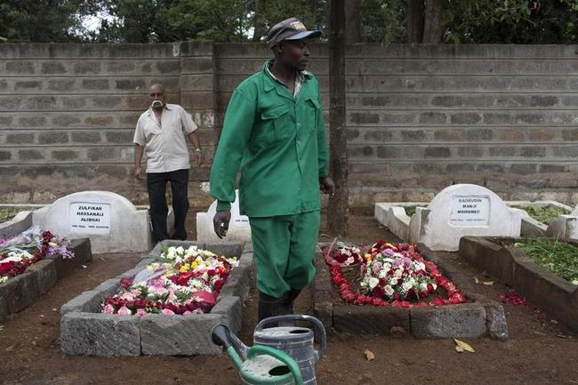 A cemetery worker walks between fresh graves of Westgate Shopping Centre shooting victims in Nairobi