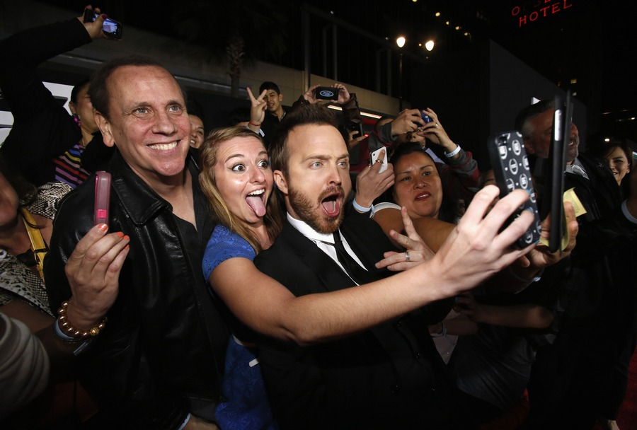 Cast member Aaron Paul (C) poses for