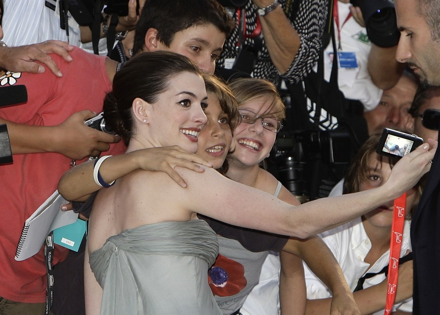Anne Hathaway takes a picture of herself and her fans as she arrives for the red carpet at the Venice Film Festival September 3, 2008. Hathaway stars in the movie