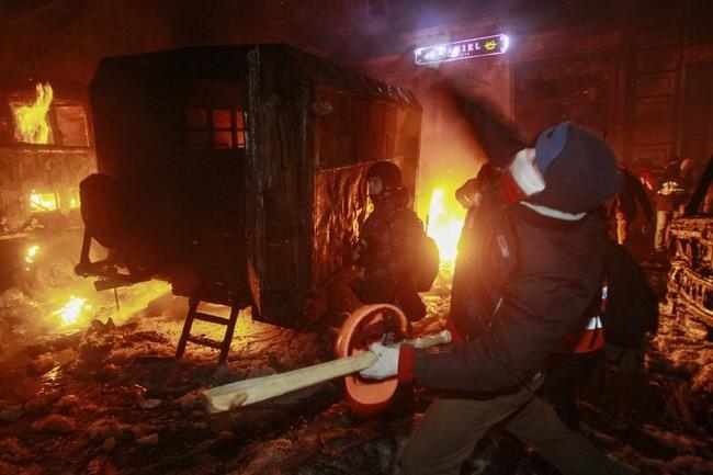 A pro-European protester throws a missile at Ukrainian riot police in Kiev