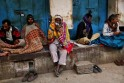 Migrant labourers covered in blankets sit in front of closed shops on a cold winter morning in the old quarters of Delhi