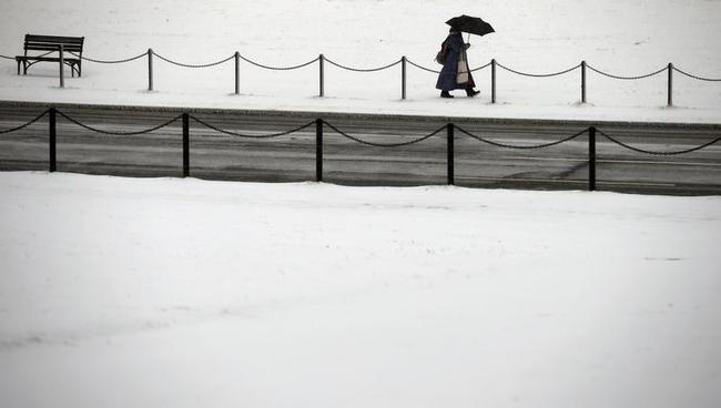 A woman walks in the snow along the National Mall as a snow storm hits Washington DC