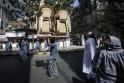 Man carries furniture on his head through a street in Mumbai