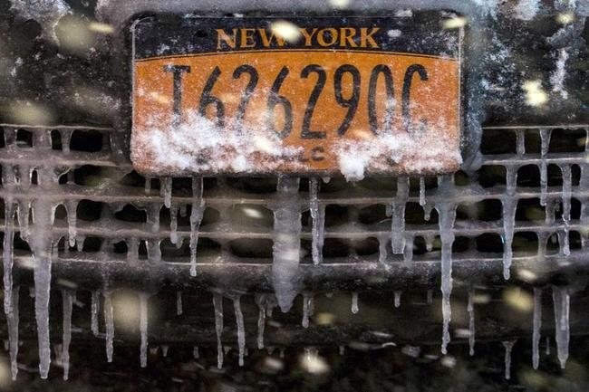 A snow and ice covered license plate is seen on a taxi in Times Square during a snow storm in Manhattan in New York