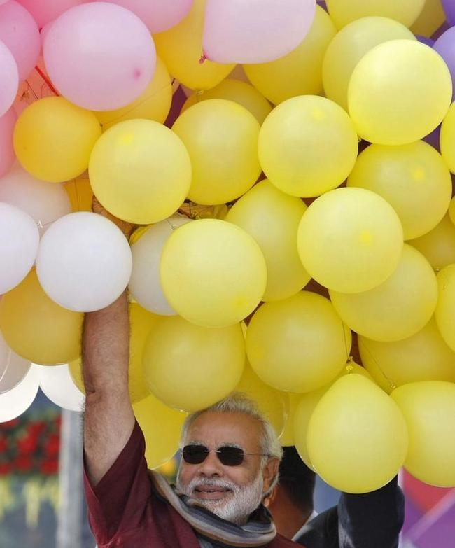 Hindu nationalist Narendra Modi holds balloons during the international kite festival in Ahmedabad