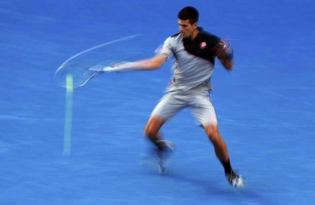 Novak Djokovic of Serbia hits a return to Stanislas Wawrinka of Switzerland during their men