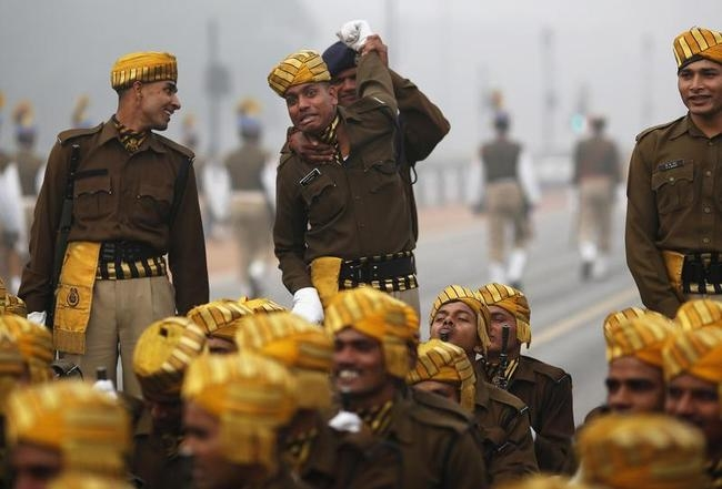 An Indian soldier stretches arm of his comrade during rehearsal for Republic Day parade amid fog on cold winter morning in New Delhi