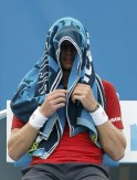 Jarkko Nieminen of Finland sits under a towel during his men's singles match against Fabio Fognini of Italy at the Australian Open 2014 tennis tournament in Melbourne