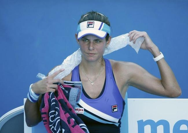 Julia Goerges of Germany uses a towel during her women's singles match against Sara Errani of Italy at the Australian Open 2014 tennis tournament in Melbourne