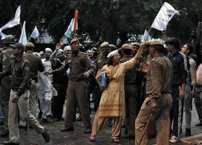 A supporter of AAP shout slogans as she shows a flag towards the Indian policemen during a protest outside the headquarters of BJP in New Delhi