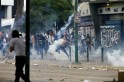 An anti-government protester throws a gas canister back at police during riots at Altamira square in Caracas