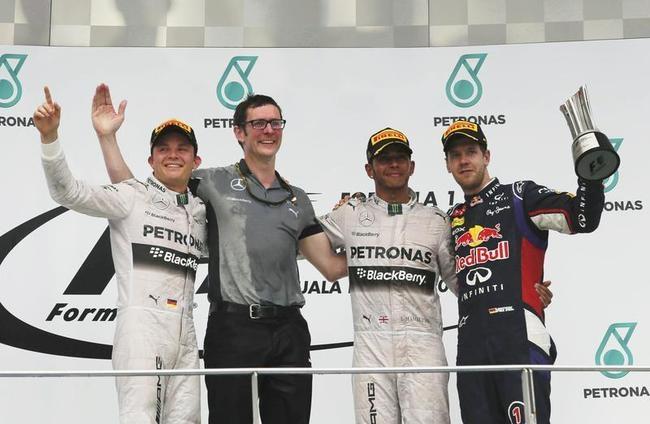 Hamilton celebrates on the podium with Rosberg, Vettel and Shovlin after winning the Malaysian F1 Grand Prix at Sepang International Circuit outside Kuala Lumpur