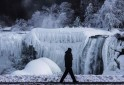 A man walks in front of partially frozen American side of Niagara Falls on during sub-freezing temperatures in Niagara Falls