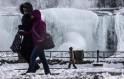 People walk in front partially frozen American side of Niagara Falls on during sub-freezing  temperatures in Niagara Falls