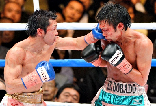 Challenger Akira Yaegashi of Japan (L) punches defending champion Toshiyuki Igarashi of Japan (R) during their World Boxing Council (WBC) flyweight title bout in Tokyo