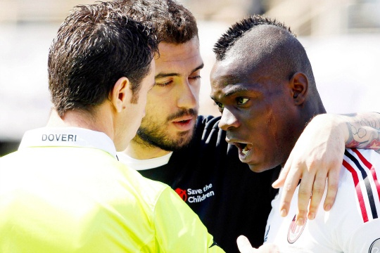 Fiorentina's Viviano embraces AC Milan's Balotelli who is arguing with assistant referee Doveri in Florence