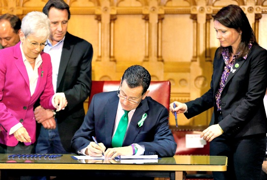 Connecticut Governor Dannel P Malloy signs legislation at the Capitol in Hartford, Connecticut, that includes new restrictions on weapons and large capacity ammunition magazines