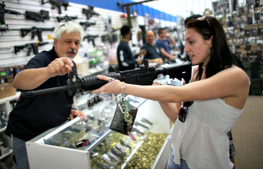 As the U.S. Senate takes up gun legislation in Washington, Dr. Gary Lampert (L), a co-owner of the National Armory gun store, helps Cristiana Verro consider fire arms