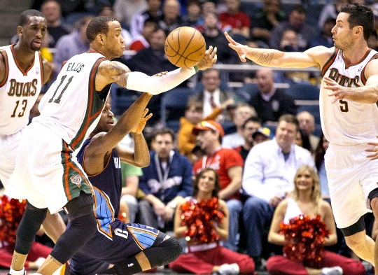 Milwaukee Bucks' Monta Ellis makes a steal in to the hands of teammate J.J. Redick as Charlotte Bobcats' Kemba Walker tries to grab the ball