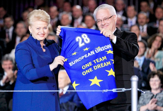 Croatia's President Josipovic holds a shirt he received from Lithuania's President Grybauskaite