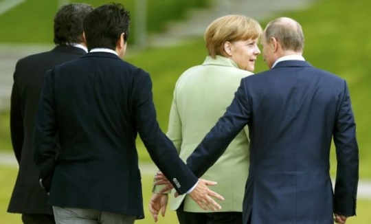 Japan's Prime Minister Shinzo Abe touches hands with Russia's President Vladimir Putin as they walk with Germany's Chancellor Angela Merkel