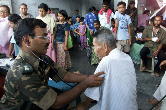 Indian Army doctor looks at old man in Manipur