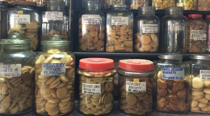 biscuits are still stored in large glass jars placed on wooden shelves at Kyani